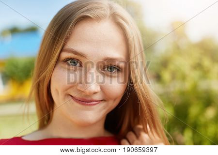 Close-up portrait of fair-haired woman with green alluring eyes freckles smiling having dimples on cheeks looking happily directly into camera isolated over green background standing outdoors