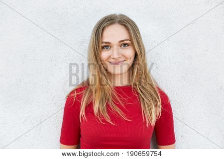 Portrait of good-looking young woman with straight blonde hair warm green eyes and dimples on her cheeks wearing red T-shirt isolated over white background. People lifestyle beauty concept