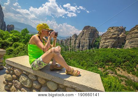 Traveler female photographer with professional camera takes shot of monasteries of Meteora overlook, Central Greece, Europe. Woman photographing a popular greek landmarks. Europe travel destinations.