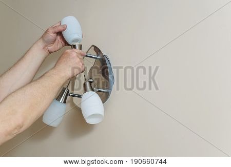 Electrician's hands are instilling a wall lamp with led bulb.