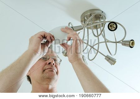 Electrician is attaching a plafond to a seiling lamp.