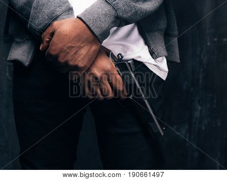 Unrecognizable armed black gangstercloseup studio shoot. Criminal man with gun in hand on dark background. Outlaw, ghetto, murderer, robbery concept