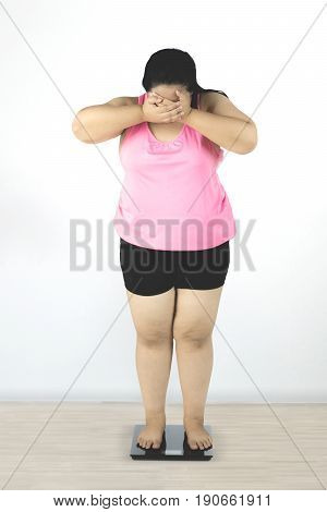 Diet concept. Full length of depressed overweight woman standing on scale while closing her face and looks sad after fail to lose weight