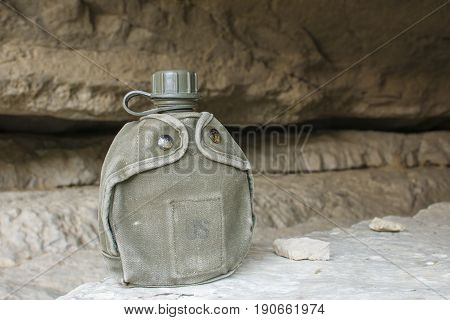 Canvas covered U.S. army canteen sits on rock at entrance to rocky cave in natural lighting