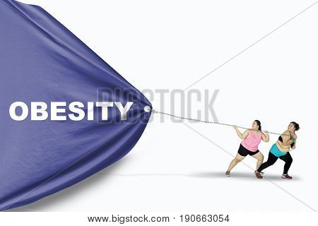 Two fat young women dragging a big banner with Obesity text while wearing sportswear isolated on white background