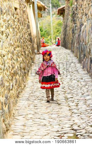 Ollantaytambo, PERU - 25 APRIL 2017: Beautifull young quechua girl walking on the streets of the city. Ollantaytambo was the royal estate of Emperor Pachacuti who conquered the region