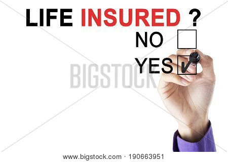 Businessman's hand selecting a yes box with a marker for a question of life insured isolated on white background