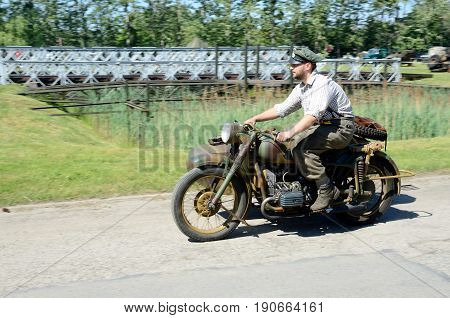 WROCLAW POLAND - JUNE 3: Reconstruction groups rally. Militarians fan gathering people in uniforms historical vehicles and weapons. Man driving German motorcycle from World War II on June 3rd 2017 in Wroclaw.