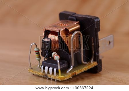 Automotive relay with details on a wooden table.