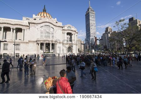 MEXICO CITY MEXICO - APRIL 19 2017: The beautiful open plaza around Palacio de Bellas Artes (Palace of Fine Arts and Torre Latinoamericana (Latin-American Tower) is a popular gathering place for locals and tourists alike.