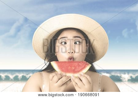 Summer holiday concept. Overweight woman looking at fresh watermelon with squint-eyed on the beach