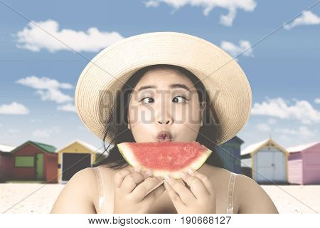Summer holiday concept. Overweight young woman with squint-eyed holding a slice of fresh watermelon and wearing hat on the beach