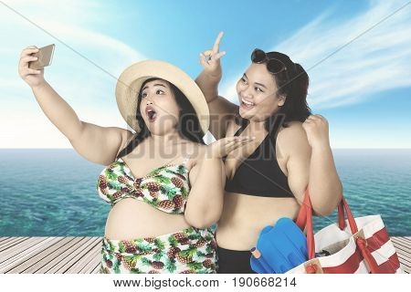 Two young women taking selfie picture on the bridge while holding beach items on bag