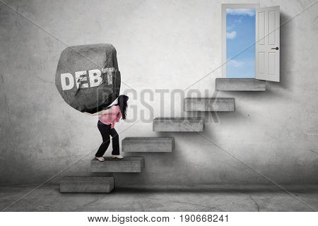 Female worker carries a boulder with Debt word on her back while walking on the stairs toward a door