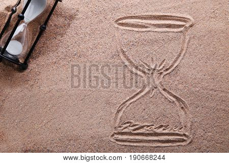 Hourglass drawn on the beach sand, close up
