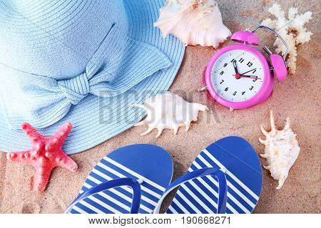 Pink alarm clock with seashells flip flops and hat on beach sand