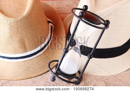 Black Hourglass With Hats On The Beach Sand