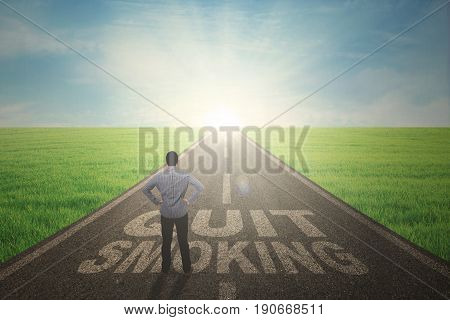 Back view of young male standing on a text of quit smoking while looking at the sunbeam on the end road