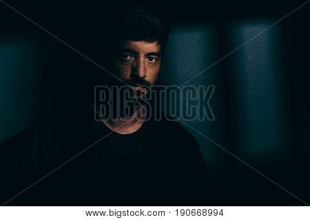 Prisoner Man In Dark Cell Illuminated Only By A Beam Of Light