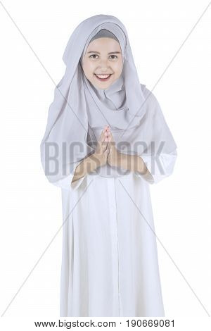 Portrait of young muslim woman standing with welcoming gesture isolated on white background