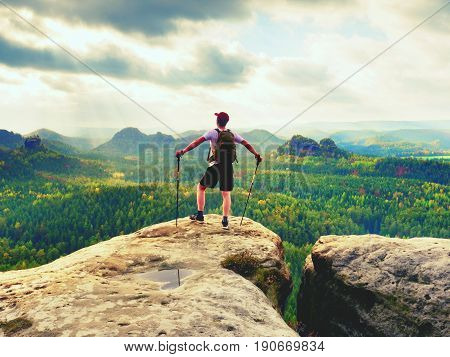 Tourist Guide On Rocky View Point With Poles In Hand. Hiker With Sporty Backpack Stand On Rock