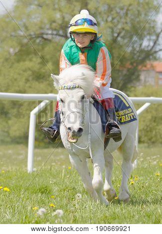 STOCKHOLM SWEDEN - JUNE 06 2017: Young jockey on pony gallop race smiling at Nationaldags Galoppen at Gardet. June 6 2017 in Stockholm Sweden