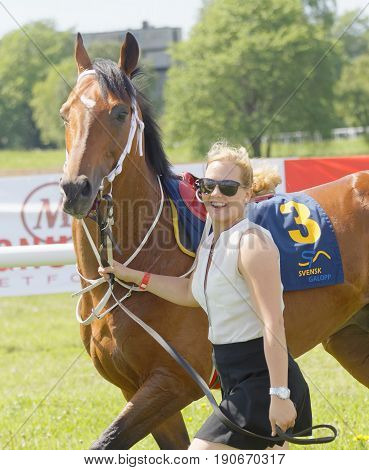 STOCKHOLM SWEDEN - JUNE 06 2017: Smiling woman leading a gallop arabian race horse in the vault at Nationaldags Galoppen at Gardet. June 6 2017 in Stockholm Sweden