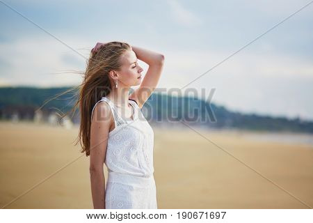 Beautiful Young Woman Enjoying Sun On A Sand Beach