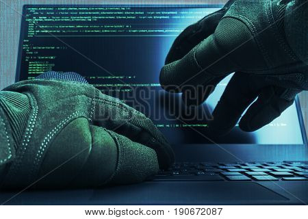 Hacker hands wearing gloves working on a console commands. Internet cyber concept. Green toning.