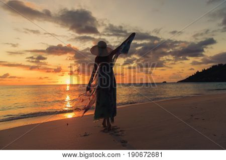 Back view of lonely girl with summer dress and hat is walking along coastline. Silhouette young woman on the beach at sunset. Fluttering dress.
