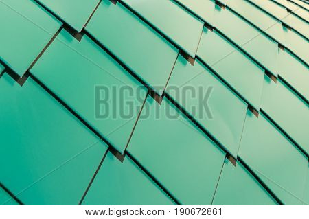 Metal shingles on the roof in the form of diamonds going to overlap. Metal sheets are flat painted green. The diamonds are in a row diagonally.