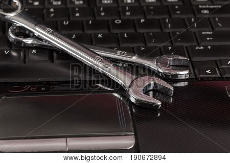 Wrench Tool And Screwdrivers Over A Laptop