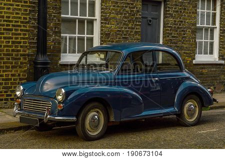 London, England - June 3, 2017: Blue Car Morris Minor 1000 Parked In An Old Street With Houses In Th