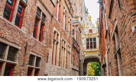 Bridge crossing between buildings over narrow Blinde-Ezelstraat, aka Blind donkey street, near Burg square, Bruges, Belgium.