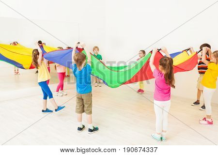Group of children standing in a circle and waving parachute in gym