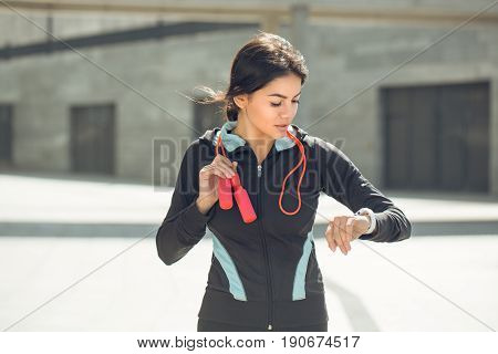 Young femaleactive exercise workout on street outside with skipping rope