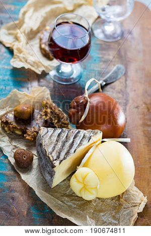 Sweet dessert liqueur wine in glass hard cheeses Caciocavallo or Provolone Tomme de Montagne dried figs with figs bread still life on wooden platter