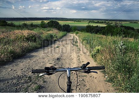 First person view on a sport bicycle before descending into the landscape valley