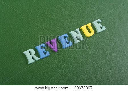 REVENUE word on green background composed from colorful abc alphabet block wooden letters, copy space for ad text. Learning english concept