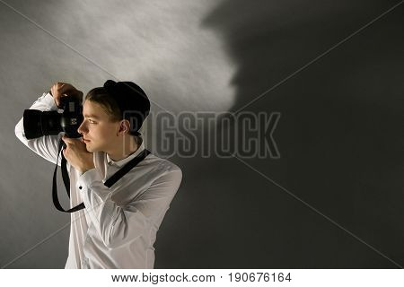 Man is photographing with camera. Studio shot of young photographer focusing with a camera on a side. Free space on grey wall