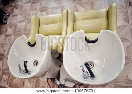 A Row Of Hair Washing Sinks. White Washbasins For Hairdresser