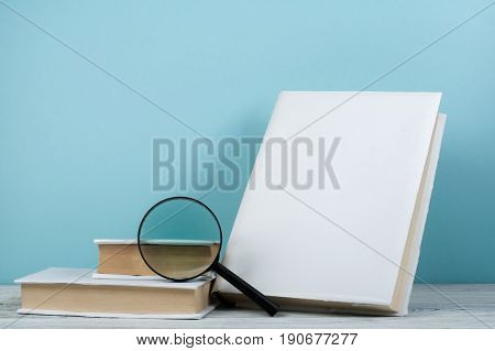 Open book, hardback colorful books on wooden table. Magnifier. Back to school. Copy space for text. Education business concept