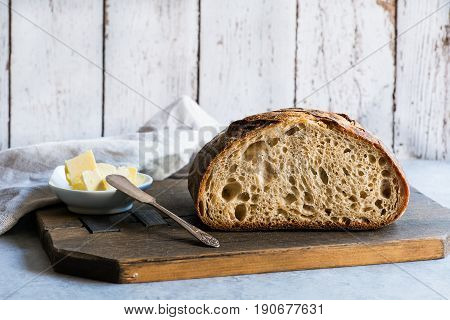 Loaf of homemade whole grain wheat sourdough bread on light background horizontal