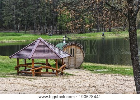 Lithuania, Druskininkai - 04/30/2016: On the shore of the forest lake there is a bathhouse and a gazebo