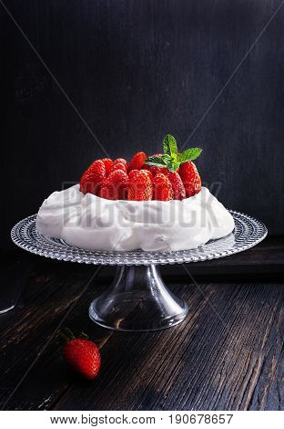 Pavlova - meringue cake with fresh strawberries on glass cake stand on old vintage black wood background. Top view copy space close up selective focus.