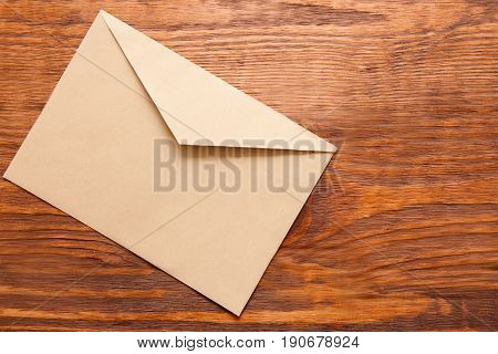 Blank brown envelope on wooden background top view. Office supplies, news, new message concept