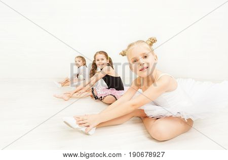 Three little ballerinas, six years old girls in dancewear, sitting on the floor against blanked background of light dance hall