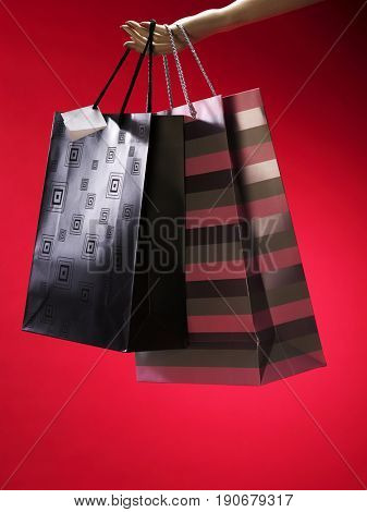 Hand holding paper bag, with red background