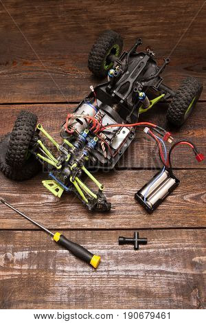Dismantled broken Rc radio control car crawler model toy repair. Green toy suv in repairshop workplace, top view