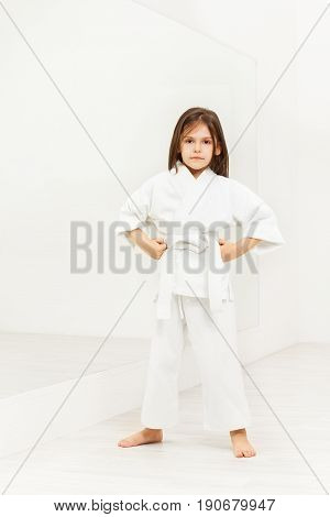 Full length portrait of karate girl in white kimono standing with hands on hips in light gym